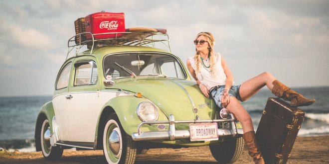 Die besten Autoreifen für den Sommerurlaub: Frau lehnt sich an alten Käfer mit neuen Reifen